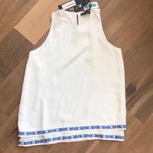 White tank top with blue embroidered detail.